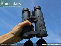 Hand holding the Athlon Ares 10x42 Binoculars