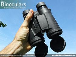 Hand holding the Upland Optics Perception HD 10x42 Binoculars